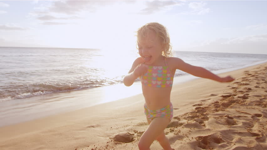 An adorable little girl runs down the beach toward her mother for a big hug and kiss. Close up shot. - HD stock footage clip