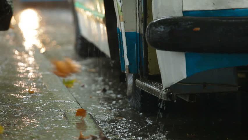 Closing bus doors at the bus stop under rain