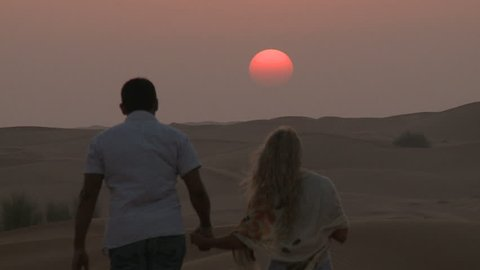 Couple in love walk against Sunset