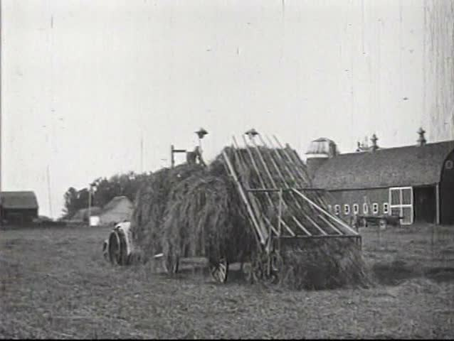 1920s - A farmer using an old fashioned hay baling method is convinced to use a tractor, in 1924.