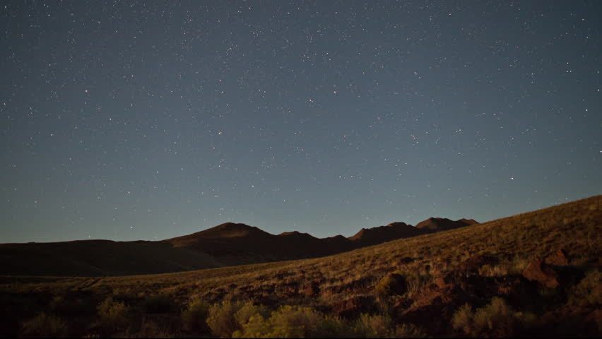 Time lapse of stars and moon lit sagebrush covered hills on a clear night in Utah