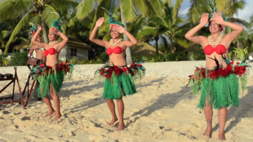 Polynesian Pacific Island dance and music group in colorful costumes dancing on tropical beach with palm trees in the background
