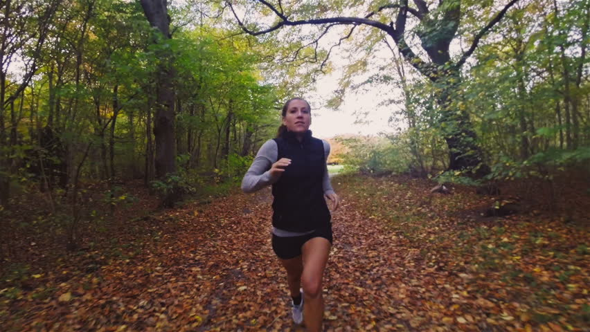 Active woman trail running in forest in the fall / autumn season. Exercising for a healthy body. Model is caucasian in the 20s.