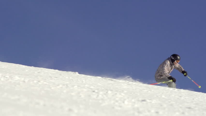 Slow Motion Of Skier Carving Fast Down The Snowy Hill With Snow Drifting Behind