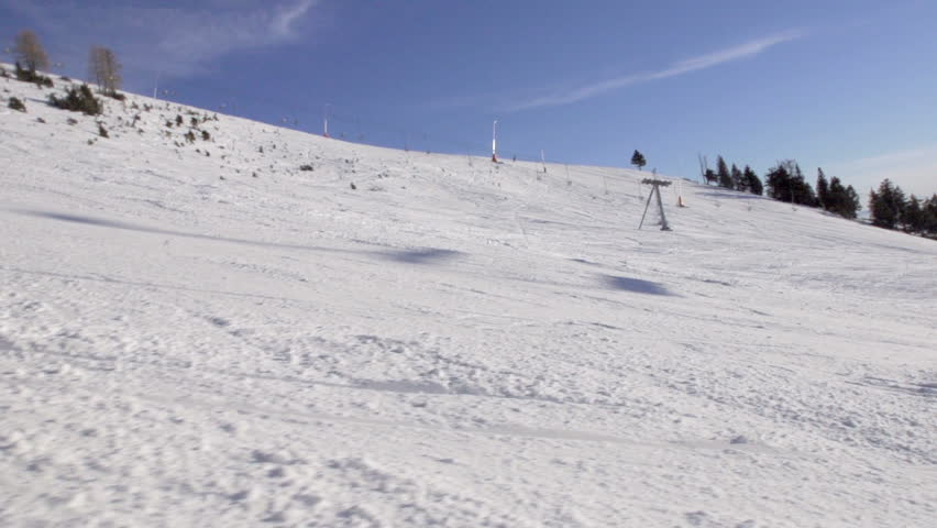 Slow Motion Shot Of Skier Falling Down On The Ski Track With Snow Spraying Around Him.