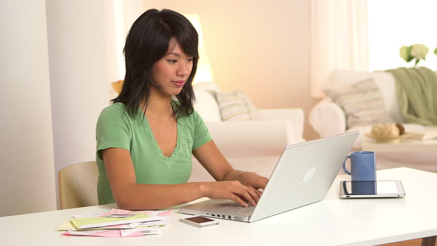 Asian woman paying bills with laptop computer and credit card