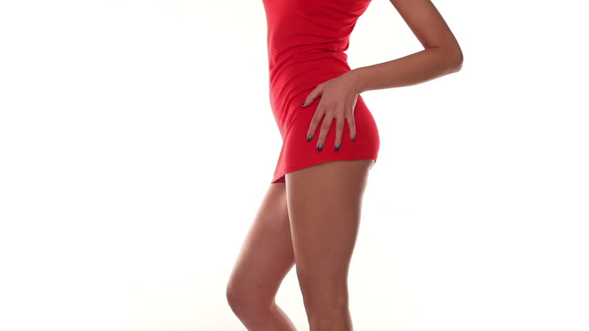 Close up view of the shapely body of a young woman in a short sexy red mini skirt giving a glimpse of her buttocks dancing against a white studio background