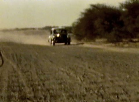 ADEN PROTECTORATE - CIRCA 1960: car on desert dirt road in the British Aden Protectorate, southern Arabia. Vintage 8mm footage. Today territory is the Republic of Yemen.