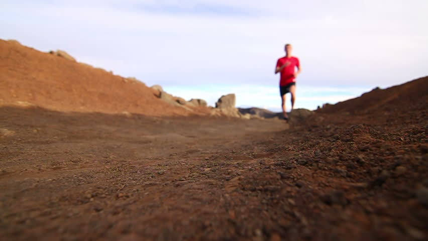 Slow Motion: low angle of young blonde fit male running on dirt trail.