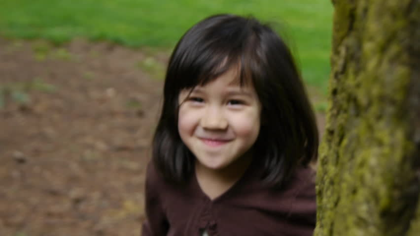 Cute Little Girl Smiles, Walks Around Tree