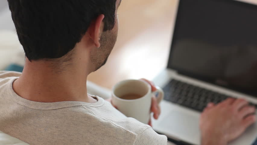 Man drinking coffee while using laptop at home in the living room