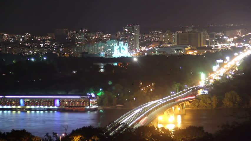Colorful night city scape bridge over river, ferry cars drive