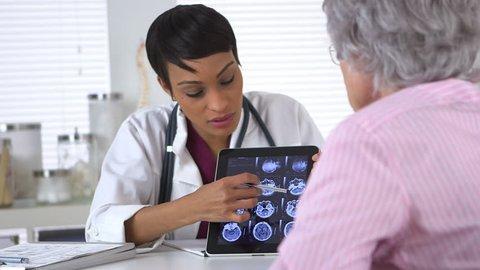 Doctor explaining brain scans to elderly woman