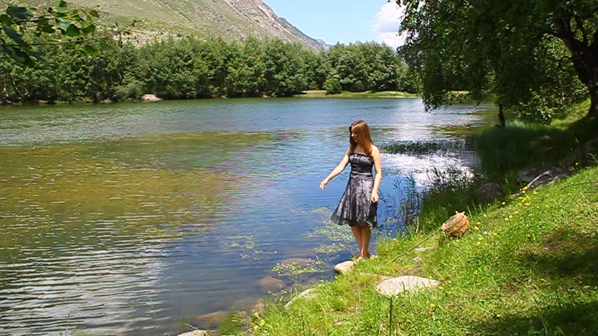 A young girl in a dress dissatisfied explains on the shore of a mountain lake #5080589