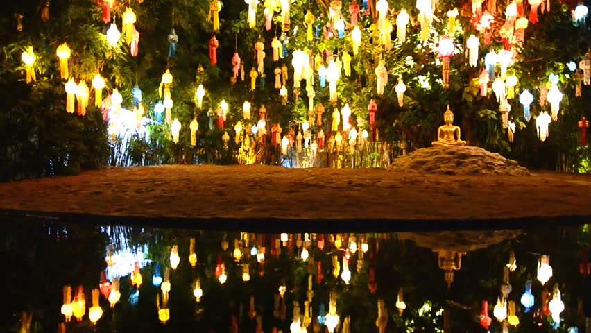 gold buddha image under beautiful lantern tree and reflection of pond (zoom out)
