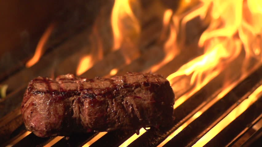 Steak on grill with flames - slow motion shot