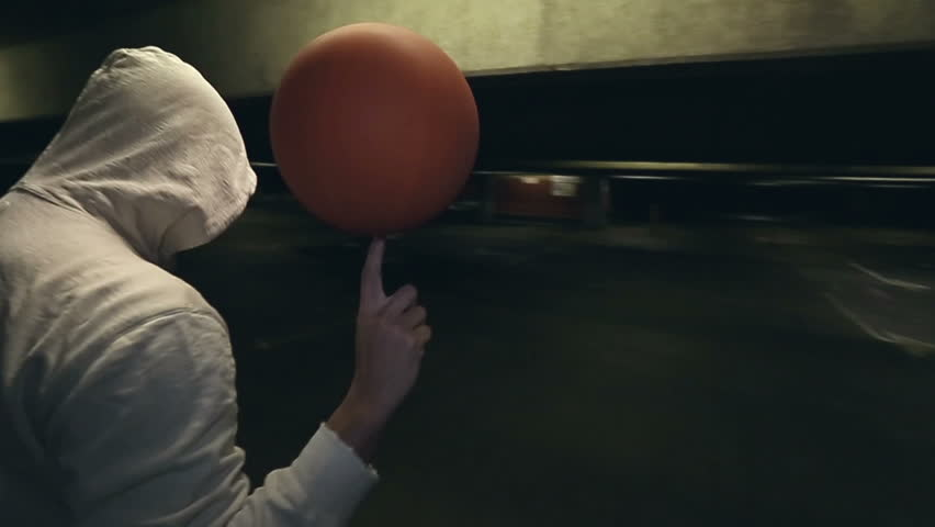 Hooded Street ball basketball player spinning the ball whilst the camera circles him