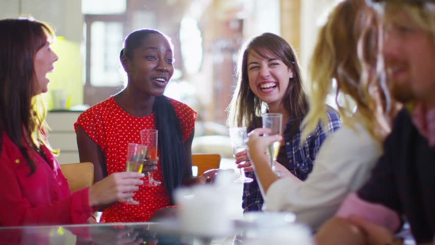 Happy group of female friends socializing and gossiping over drinks in a relaxed environment.