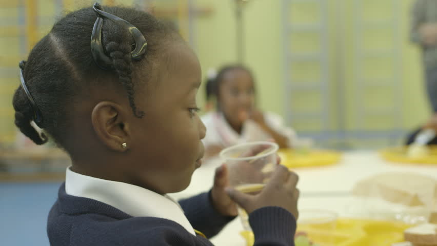 CU A girl drinking water and smiling in canteen