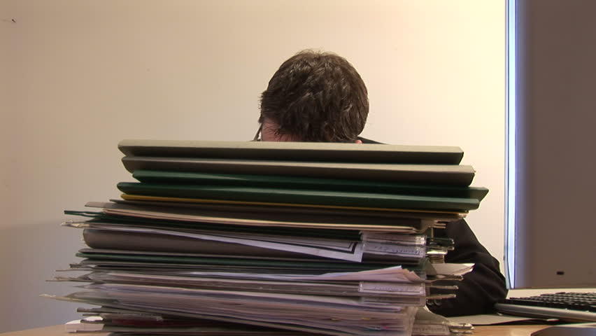 Businessman at Work With Stack of Documents