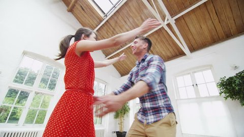 Happy young couple viewing a potential new home. In slow motion.