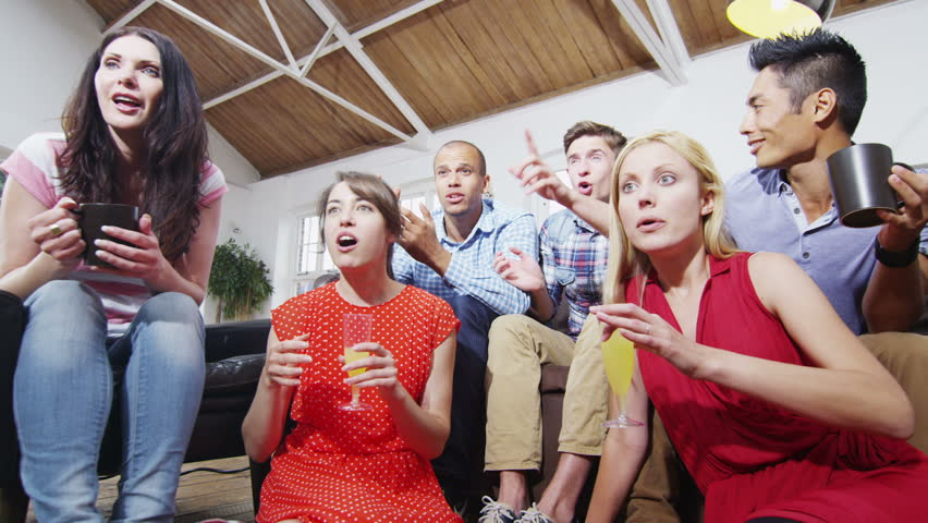 Happy diverse group of friends watching sports on TV and cheering on their team. In slow motion.