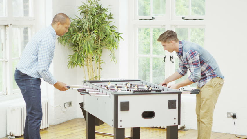 Happy male friends hanging out together and playing a game of table football.    Shutterstock HD Video #5099939