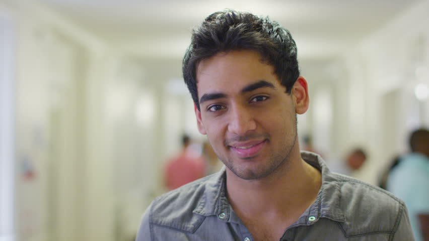 Portrait of a happy male indian student standing in a  busy hallway with other students and teachers walking in the background. In slow motion.
