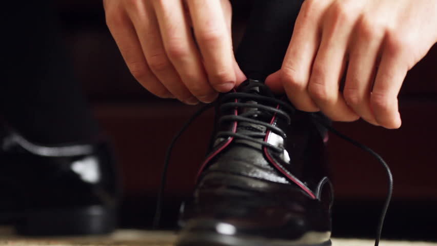 Close-up of tying the laces on expensive shoes