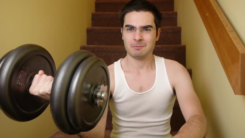 Young man exercising at home with dumbbells
