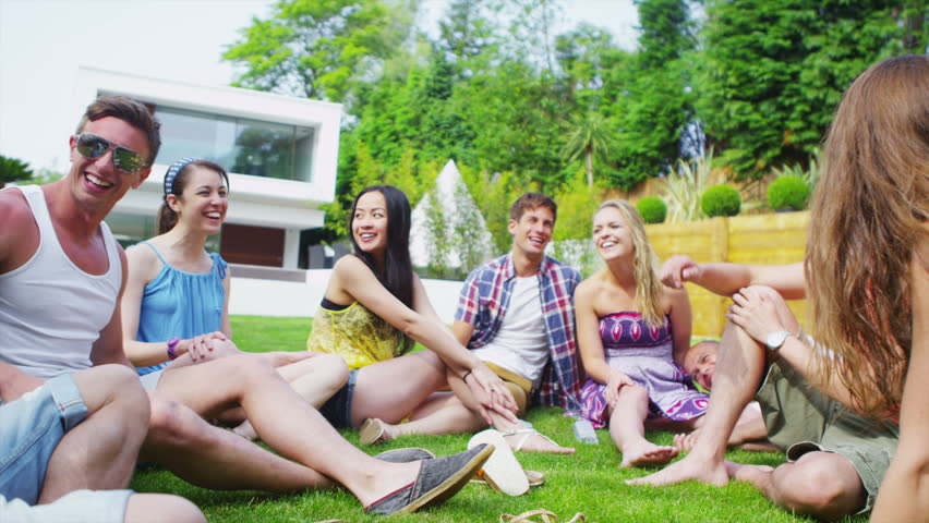 Cheerful group of young friends relaxing outdoors and chatting together on a summer day. In slow motion.
