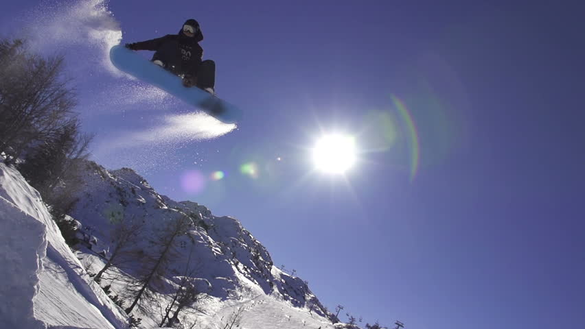 SLOW MOTION: Snowboarder jumping over the sun #5120339