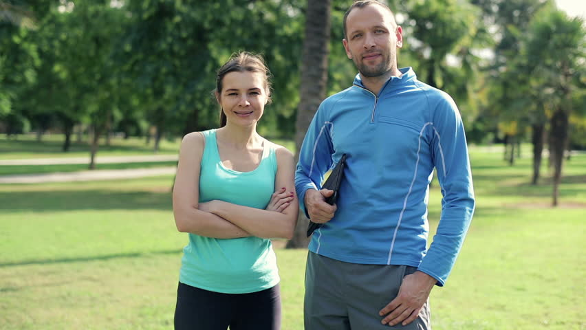 Happy young sporty couple standing in the park