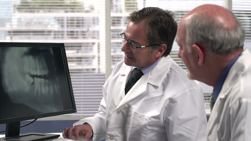 Two male dentists looking at an x-ray | Shutterstock HD Video #5146529