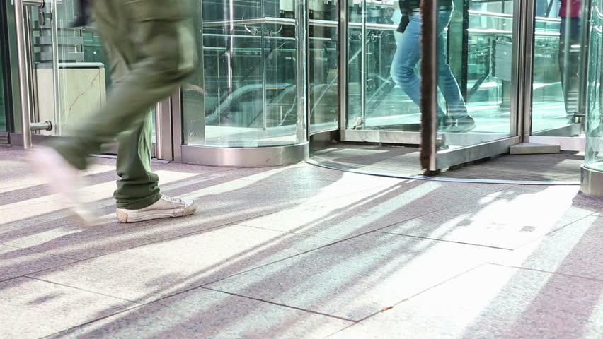 People Walking through a Revolving Door