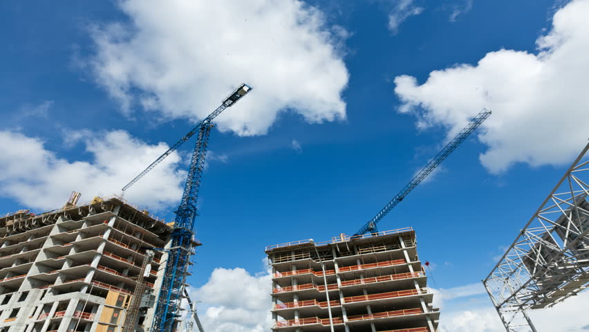 Time lapse of construction cranes. Time lapse of a modern office or residential building being built with clouds and blue sky in background