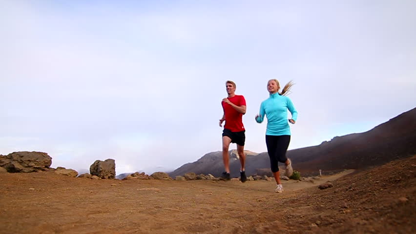 Couple Running - young happy fit couple running outside in nature. Low angle filmed in slow motion
