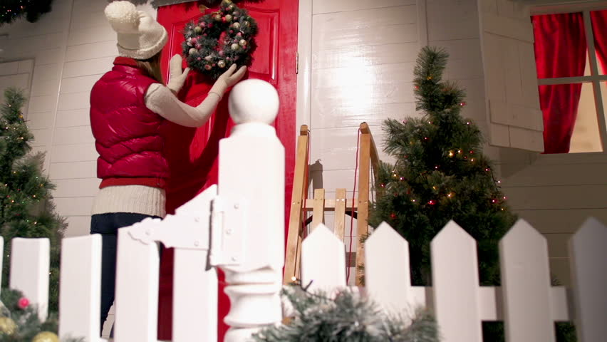 Young woman is decorating the front door of the house with a fur wreath on a