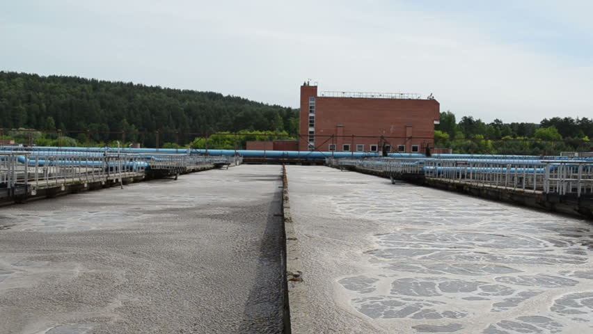Water treatment facility plant with large pools basins of dirty sewage water. Aerated grit chamber cleaning stage.