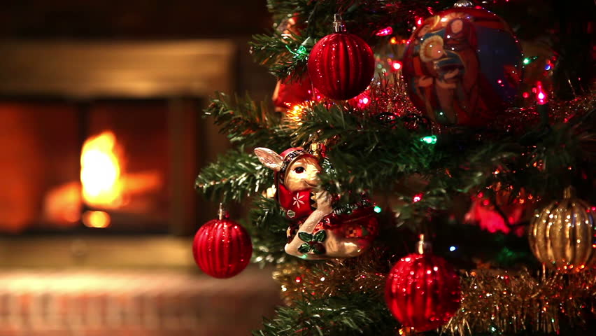 Camera is Tracking Across a Christmas Tree Full of Ornaments Standing in a Living Room, Revealing an Out of Focus Fire Burning in A Fireplace in the Background.