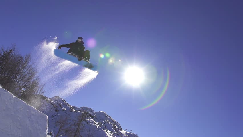 SLOW MOTION: Snowboarder jumps over kicker, low angle view #5187869