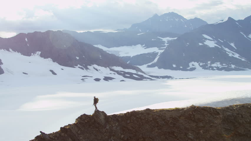 Aerial view male mountain climber ridge walking Chugach Range of mountains nr Troublesome Glacier, State of Alaska, USA shot on RED EPIC, 4K, UHD, Ultra HD resolution