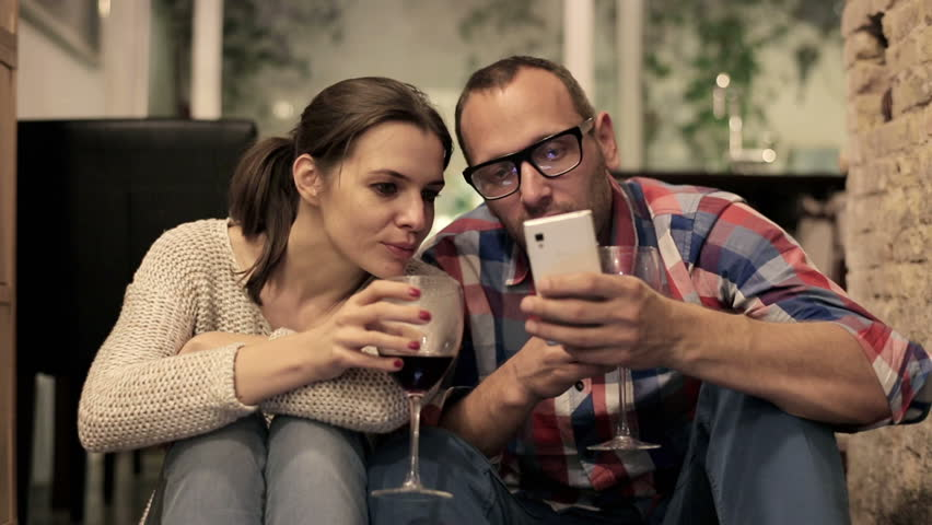 Couple drinking wine and watching funny things on smartphone