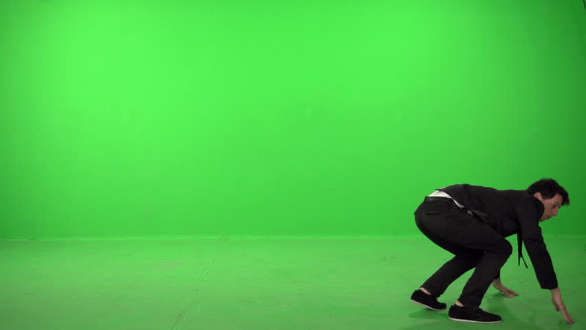 Dancer dressed as business man on a green screen in slow motion 200fps