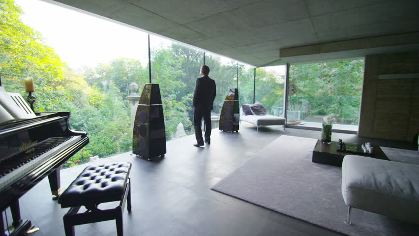 Businessman in luxury contemporary home goes to the window to look at the view. In slow motion.