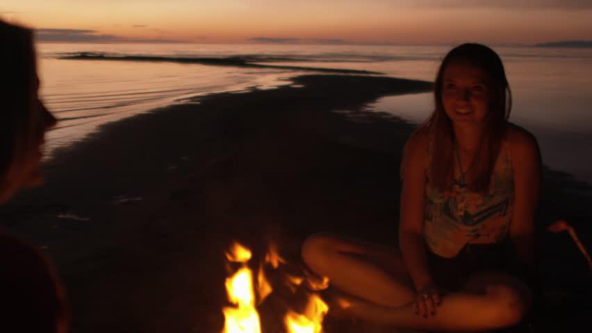 Group Of Teenage Girls Talking Around A Beach Campfire At Dusk/Night