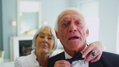 Attractive senior couple in formal evening wear are getting dressed for an evening out. Woman adjusts her partner's tie and gives him a kiss. In slow motion.