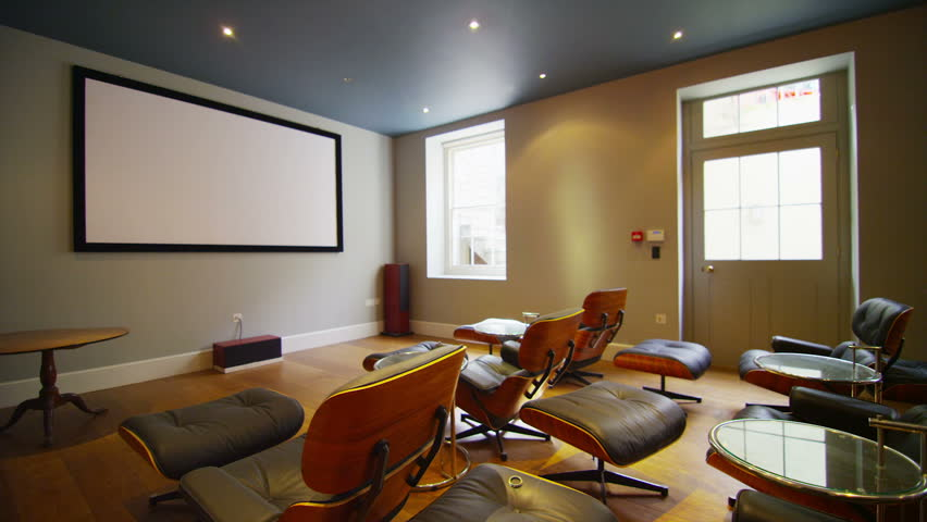 Interior view of a luxurious contemporary home television viewing area with leather reclining armchairs and wall mounted screen.