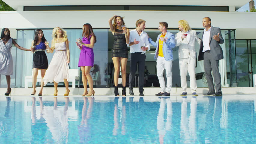 Glamorous friends enjoying drinks by the pool outside luxury modern home. In slow motion.