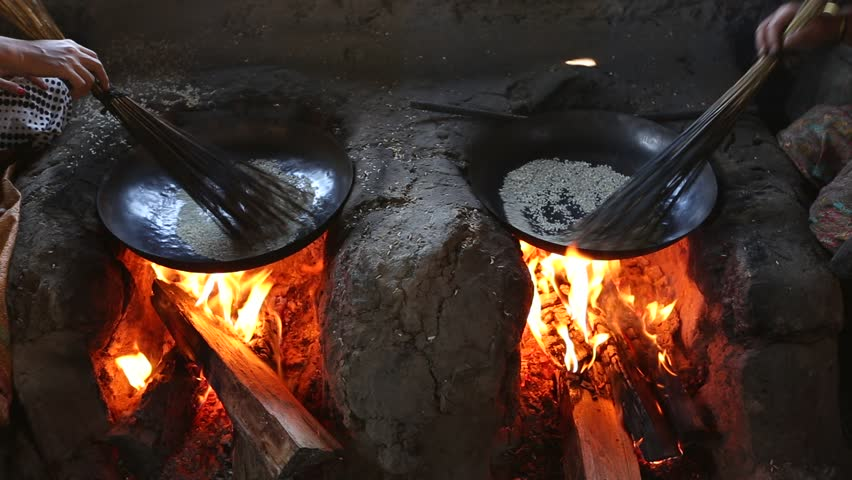 Roasting Pearl Barley in the pan over old traditional Bhutanese stove.